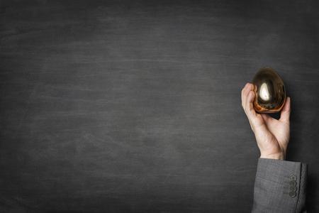 Businessman holding a golden egg in a hand on blackboard background Banco de Imagens