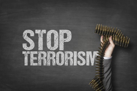 Stop terrorism text on black blackboard with businessman hand holding ammunition