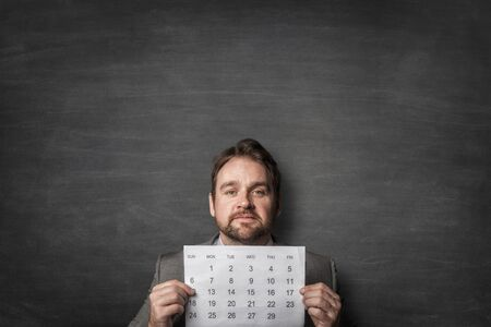 Businessman showing paper calendard in front of him