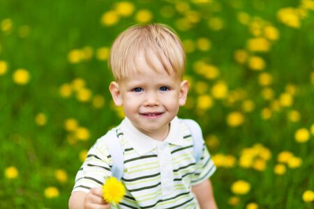 Smiling boy in dandelion meadow carrying flower. Shallow DOF effect photo