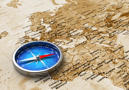 gps: Macro view of blue metal compass on the old world map Stock Photo