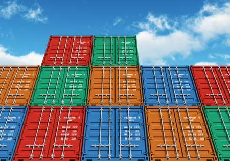 SHIPPING CONTAINERS: Stacked color cargo containers over the blue sky with clouds Stock Photo