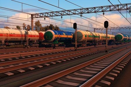cisterna: Los trenes de carga con los coches del depósito de combustible en la estación de ferrocarril en la puesta del sol
