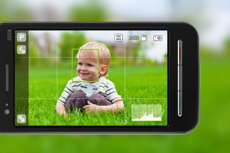 Taking pictures with mobile phone: smartphone in camera mode outdoors  photo