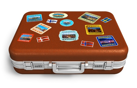 Brown leather travel suitcase with colorful labels isolated on white background  photo