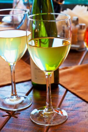 Macro view of two goblets with white wine on served restaurant table photo