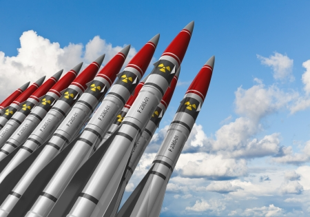 Row of heavy nuclear missiles against blue sky with clouds