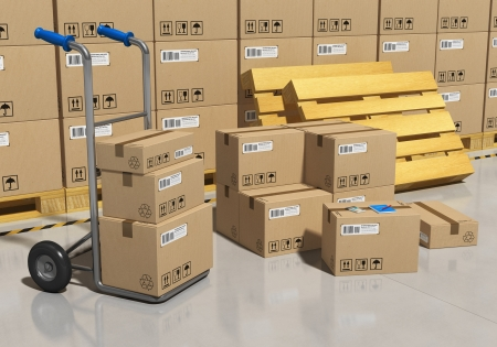 Interior of storage warehouse with goods packaged in cardboard boxes and hand truck    Stock Photo