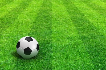 Close view of green striped football field with soccer ball photo