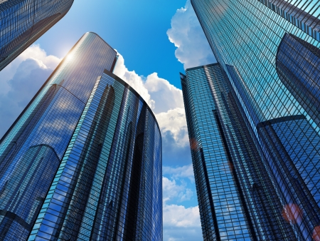 Downtown corporate business district architecture  glass reflective office buildings against blue sky with clouds and sun light  Design is my own Stock Photo