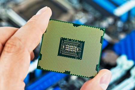 Macro view of modern multicore CPU processor in human hand with PC computer motherboard in background. Stock Photo