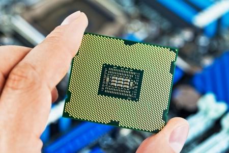 silicio: Macro vista de la actual multi-núcleo del procesador de la CPU en la mano del hombre con la placa base de PC ordenador en el fondo. Foto de archivo