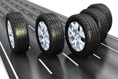 Creative automotive industrial concept: set of black car auto rubber wheels driving the asphalt highway road isolated on white background Stock Photo
