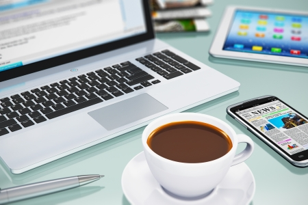 Modern office business workplace with laptop PC, touchscreen smartphone, tablet computer and white porcelain cup of black coffee photo