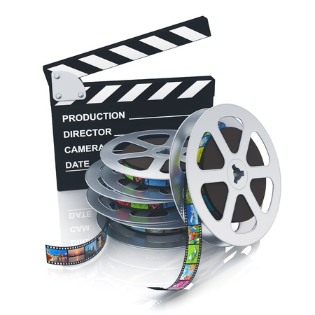 film reel: Cinema, movie, film and video media industry concept  clapper board and stack of metal film reels with filmstrips with colorful pictures isolated on white background with reflection effect Stock Photo