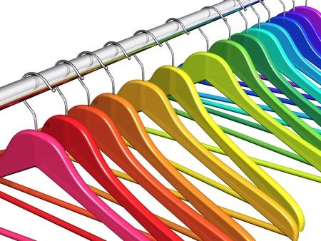 ropa colgada: Fila de color de perchas de arco iris en el metal brillante barra de colgar aislado en fondo blanco