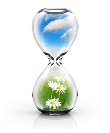 desarrollo sustentable: Ecología, medio ambiente y protección de la naturaleza concepto ahorro: reloj de arena con el paisaje natural con hierba verde y el cielo azul con nubes aisladas sobre fondo blanco con efecto de reflexión