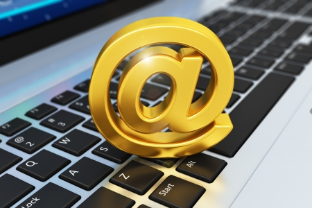 Creative e-mail, internet and web communication messaging concept  golden shiny @ symbol on business laptop or office notebook keyboard with selective focus effect photo