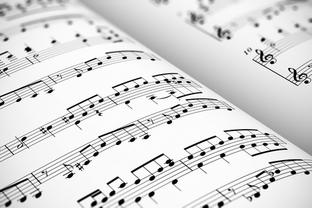 notes music: Musical concept background: macro view of white score sheet music with notes with selective focus effect