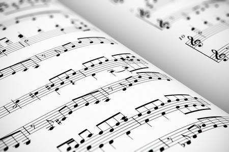 Muzikaal concept achtergrond: macro weergave van witte score bladmuziek met noten met selectieve focus effect Stockfoto