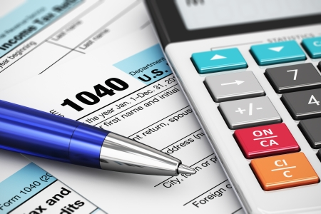 tax: Macro view of 1040 US Tax Form, calculator and ballpoint pen