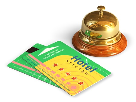 Travel and tourism concept  golden reception bell and group of color hotel keycards or cardkeys isolated on white background   photo