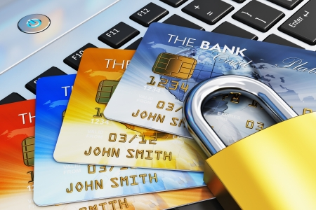Creative mobile banking, commerce and security payment financial business concept  macro view of group of color credit cards and golden padlock on laptop computer PC notebook keyboard  Design is my own and all text labels are fully abstract photo