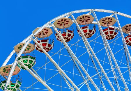 observation wheel: Scenic summer view of color Ferris observation wheel over blue sky in amusement park Stock Photo
