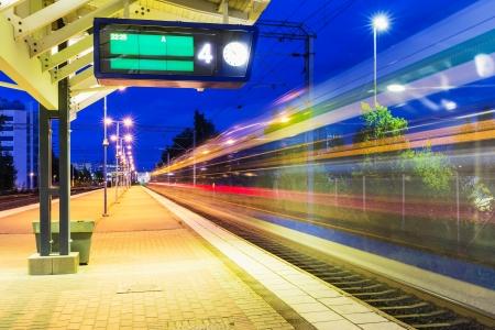Viaje del ferrocarril y la industria del transporte comercial concepto opinión de la noche de verano de tren de pasajeros de alta velocidad que salen del andén de la estación de ferrocarril con efecto de desenfoque de movimiento