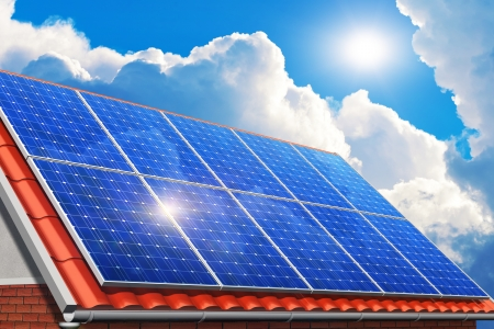 solar equipment: Creative solar power generation technology, alternative energy and environment protection ecology business concept  group of solar battery panels on red house, home or cottage tiled roof against blue sky with sun light and white clouds Stock Photo