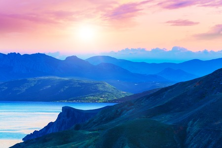 Scenic summer evening sunset in mountains landscape with sea coast photo