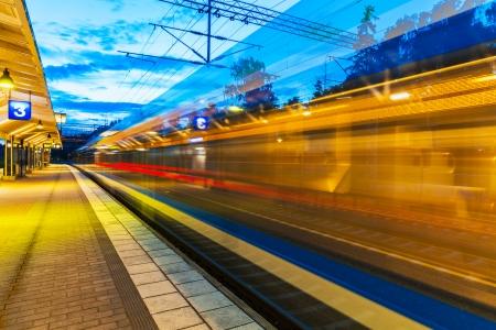 Voyage de chemin de fer et l'industrie du transport business concept été vue le soir de la vitesse de train de banlieue élevé de passagers au départ de quai de la gare de chemin de fer avec un effet de flou de mouvement Banque d'images - 23463221