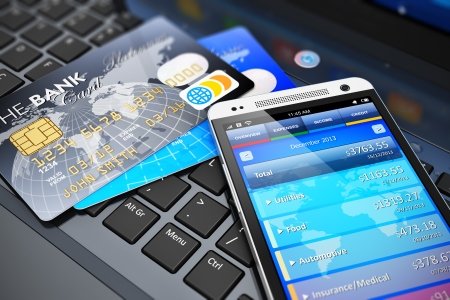 online banking: Mobile banking, financial success, accounting and electronic internet money payments business concept  macro view of stack of credit cards and modern touchscreen smartphone on office laptop keyboard with selective focus effect