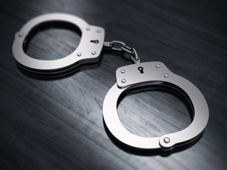 arrested criminal: Macro view of metal handcuffs on black wooden office table with selective focus effect Stock Photo