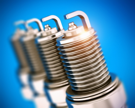 car plug: Creative car repair service and automotive transportation industry business concept  set of four metal spark plugs on blue background with selective focus effect