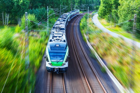 Railroad travel and railway tourism transportation industrial concept  scenic summer view of modern high speed passenger commuter train on tracks with motion blur effect photo
