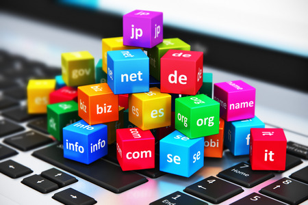 domains: Creative abstract global internet communication PC technology and web telecommunication business computer concept: macro view of group of color cubes with domain names on laptop or notebook keyboard with selective focus effect