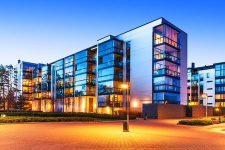 nieruchomosci: Budowa domu i mieście konstrukcji koncepcja: wieczorny widok z zewnątrz miejskich nieruchomości nowoczesne domy