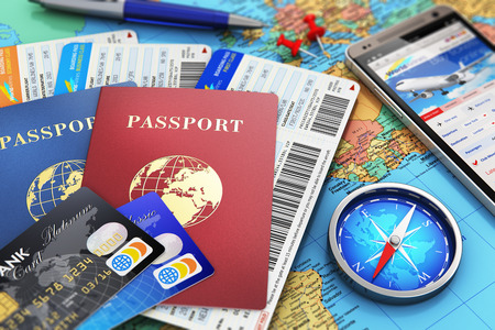 Creative abstract business travel and tourism concept: air tickets or boarding pass, passports, touchscreen smartphone with online airline tickets booking or reservation internet application, magnetic compass, credit cards and pen on world geographic map