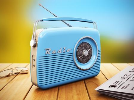 Oude blauwe vintage retro stijl radio-ontvanger, brillen en oude zwart-wit krant op houten tafel buiten Stockfoto
