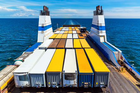 フェリー商業産業船の海でのトラックの貨物コンテナー 写真素材