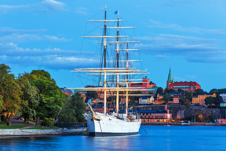 chapman: Scenic summer evening view of the Old Town (Gamla Stan) with historical tall sailing ship AF Chapman at Skeppsholmen island in Stockholm, Sweden