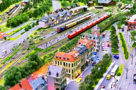scale model: Macro view of toy hobby railroad layout with railway station building, passenger and freight cargo trains on rail tracks