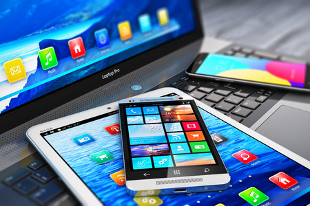 Creative abstract mobility and modern internet business communication technology concept: macro view of laptop or notebook, tablet computer PC and black glossy touchscreen smartphones with color interfaces with icons and buttons with selective focus effec