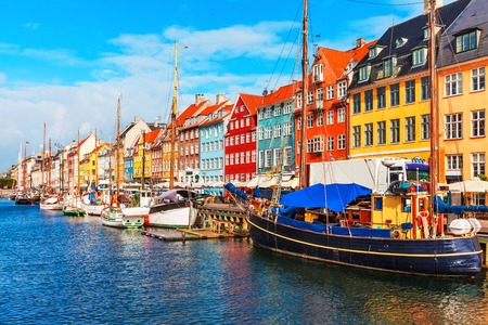 Scenic summer view of Nyhavn pier with color buildings, ships, yachts and other boats in the Old Town of Copenhagen, Denmark Фото со стока