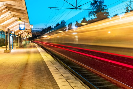 Abstrato criativo de viagens da estrada de ferro e indústria de transporte conceito: Opinião da noite do verão de alta velocidade do trem de passageiros com partida plataforma da estação ferroviária com efeito motion blur