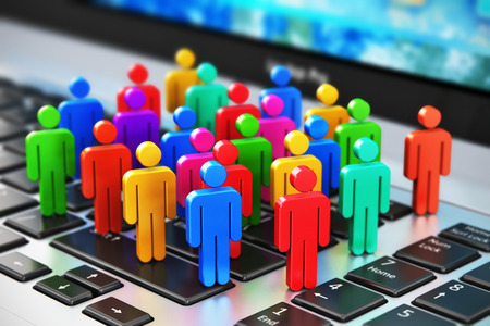 Creative abstract social media internet communication and business marketing corporate web concept: macro view of group of 3D color people figures on laptop or notebook keyboard with selective focus effect Banque d'images