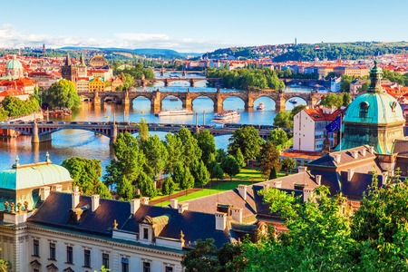 historic architecture: Scenic summer sunset aerial view of the Old Town pier architecture and Charles Bridge over Vltava river in Prague, Czech Republic