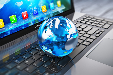Creative abstract global computer communication and internet business telecommunication concept: macro view of crystal Earth globe on laptop or notebook keyboard with selective focus effect
