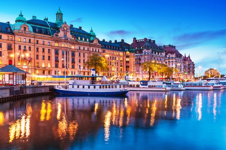 castle: Scenic summer evening panorama of the Old Town Gamla Stan architecture pier with sightseeing travel ships and boats in Stockholm Sweden Stock Photo
